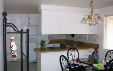 Image of white kitchen before remodel with cabinets blocking view