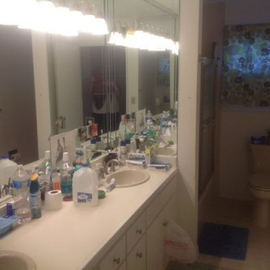 Cluttered counter bathroom before